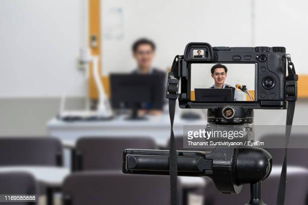 close-up of camera against man speaking on microphone - 放送 ストックフォトと画像