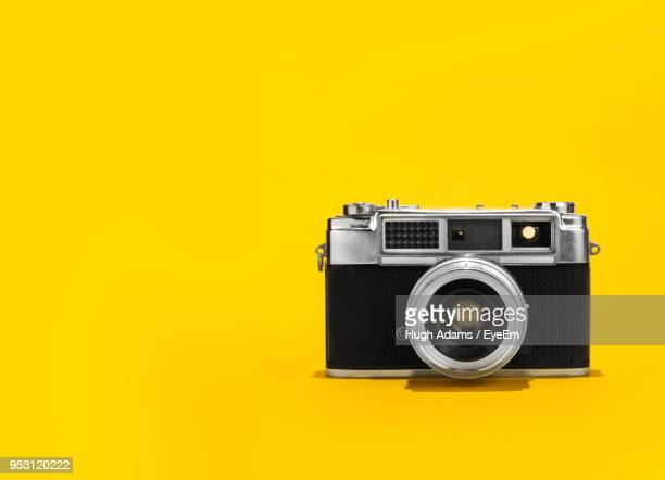 Close-Up Of Camera Against Yellow Background