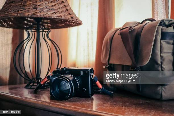 Close-Up Of Camera And Bag On Table At Home