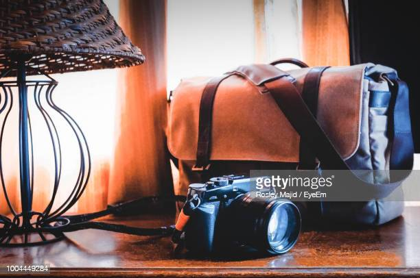 Close-Up Of Camera And Bag On Table