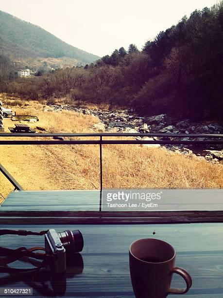 Close-up of camera and cup on table against landscape