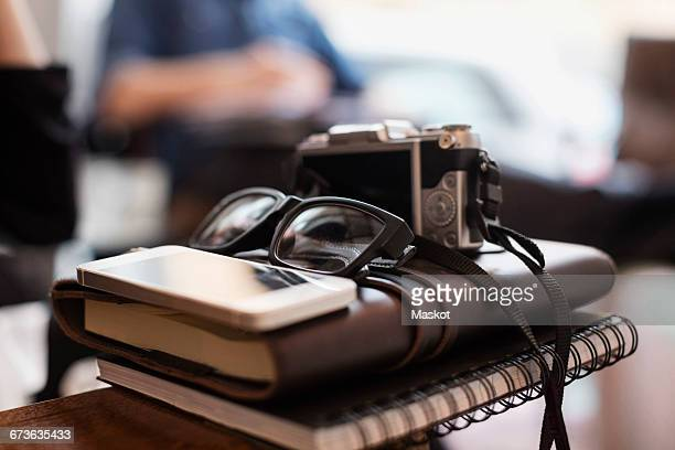 Close-up of camera and eyeglasses with smart phone on diaries at creative office
