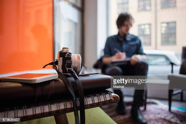 Close-up of camera and smart phone on books with man working in creative office
