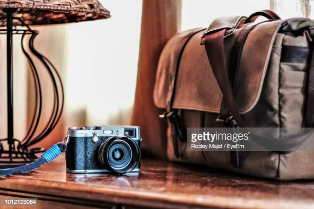 Close-Up Of Camera By Bag On Wooden Table At Home