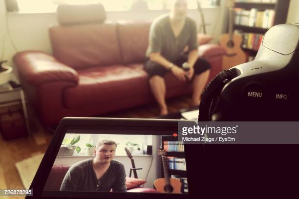 Close-Up Of Camera Filming Man Sitting On Sofa At Home