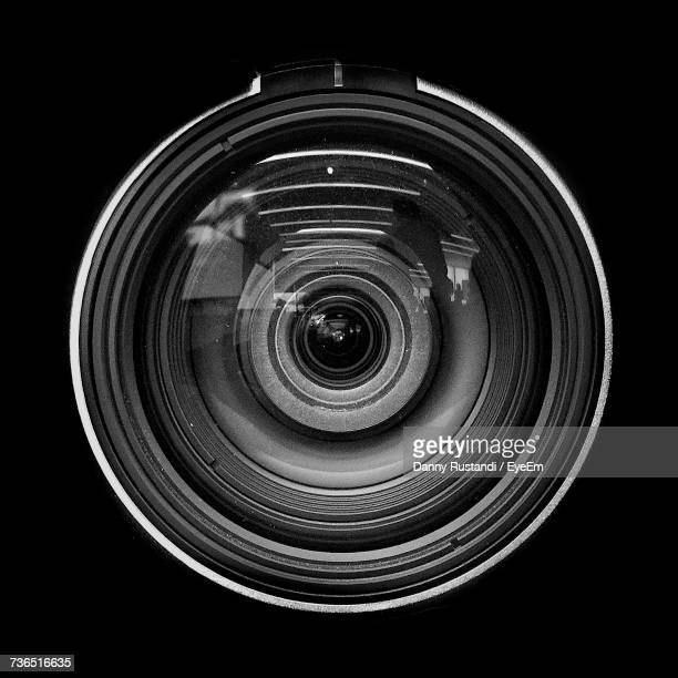 close-up of camera lens against black background - lens optical instrument stock photos and pictures