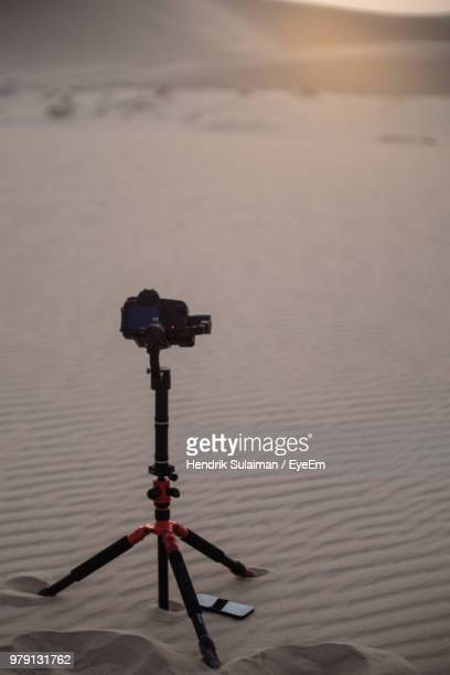 Close-Up Of Camera On Tripod At Desert During Sunset