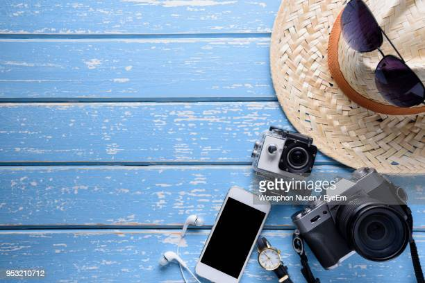 Close-Up Of Camera With Smart Phone And Hat On Table