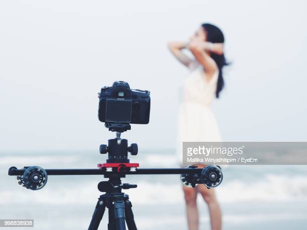 Close-Up Of Camera With Woman Standing In Background At Beach
