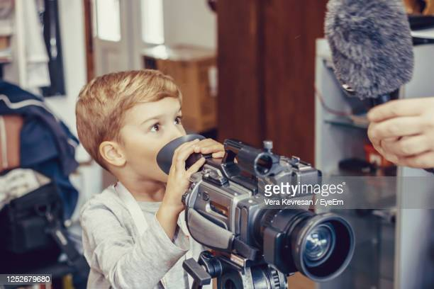 close-up of cameraman showing to a kid how to use microphone with video camera. - ディレクター ストックフォトと画像