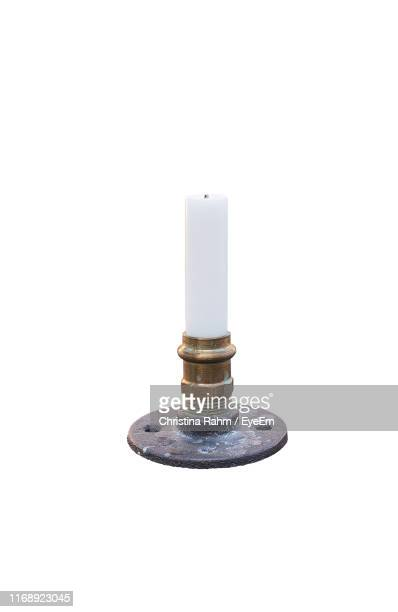 close-up of candle against white background - candlestick holder stock pictures, royalty-free photos & images