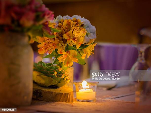 Close-Up Of Candle And Bouquet On Dinner Table