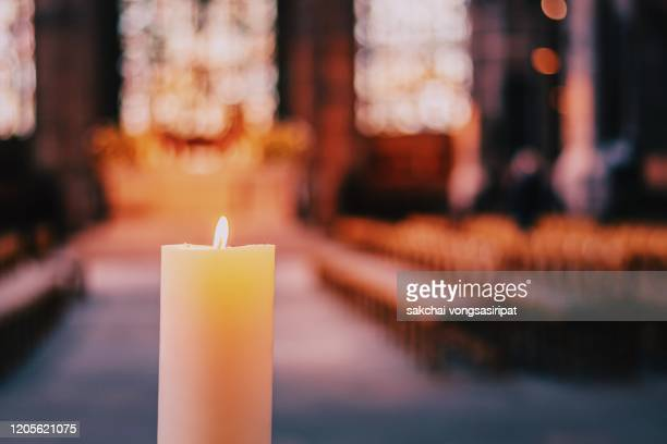 close-up of candle in the church - kirche stock-fotos und bilder