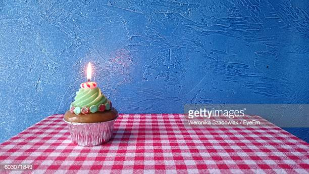 Close-Up Of Candle Lit On Cup Cake At Table