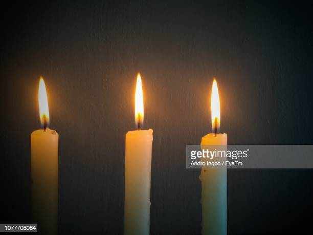 Close-Up Of Candles Burning Against Wall