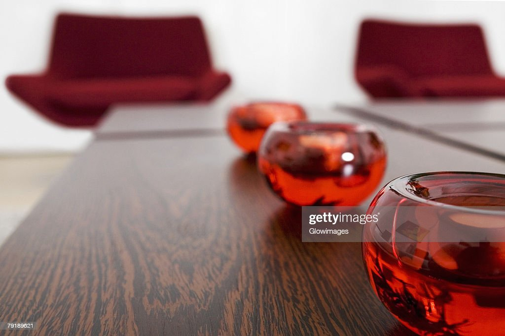 Close-up of candlestick holders in a row on a table : Stock Photo