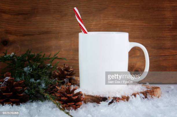 Close-Up Of Candy Cane In Mug By Twigs And Pine Cones Amidst Fake Snow On Table