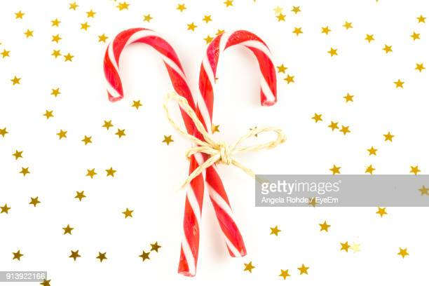 close-up of candy canes amidst stars over white background - angela rohde stock-fotos und bilder