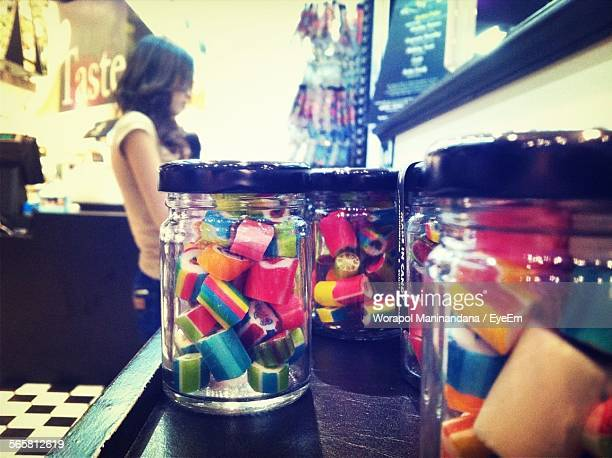 Close-Up Of Candy Jars With Woman In Background At Store