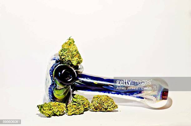 Close-Up Of Cannabis With Pipe Against White Background