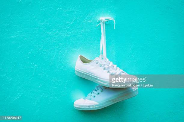 close-up of canvas shoes hanging on wall - white shoe stock pictures, royalty-free photos & images