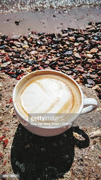 Close-up of cappuccino on beach