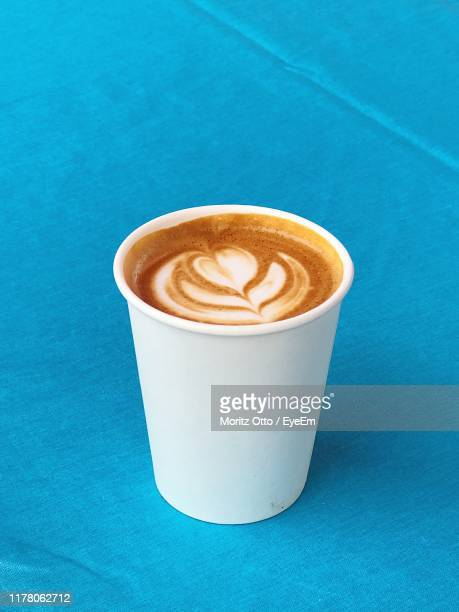 close-up of cappuccino on blue table - disposable cup stock pictures, royalty-free photos & images