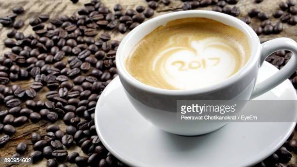 Close-Up Of Cappuccino With Roasted Coffee Beans On Table