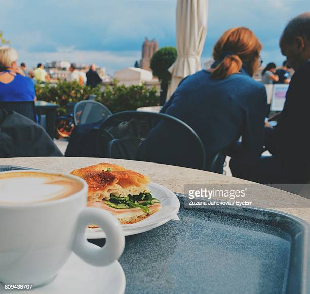 Close-Up Of Cappuccino With Sandwich Served On Table By People At Sidewalk Cafe