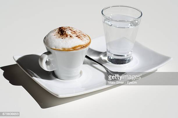 Close-Up Of Cappuccino With Water In Tray Against White Background