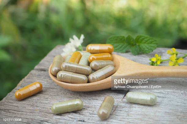 close-up of capsules in wooden spoon on table - nutritional supplement stock pictures, royalty-free photos & images