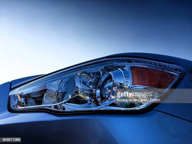 close-up of car headlight against clear sky - headlight stock pictures, royalty-free photos & images