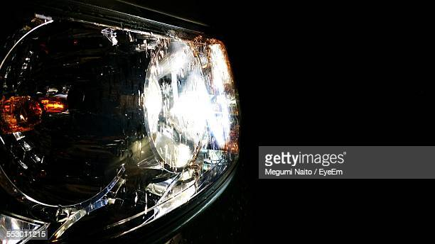 Close-Up Of Car Headlights Against Black Background