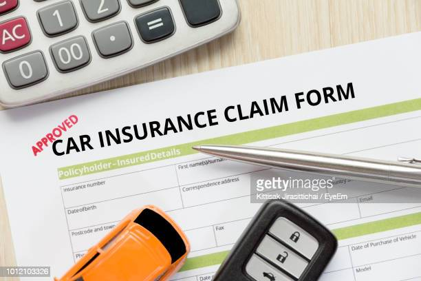 Close-Up Of Car Insurance Claim Form With Toy And Key On Table