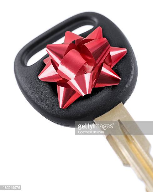 Close-up of car key with a red bow on it