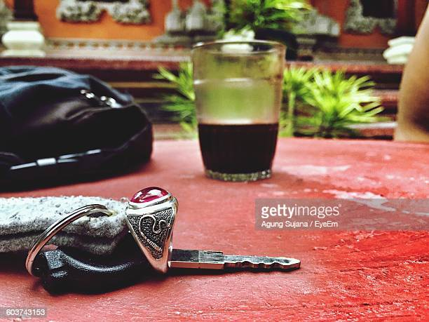 Close-Up Of Car Key With Drink On Table