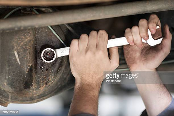 Close-up of car mechanic working with screw wrench
