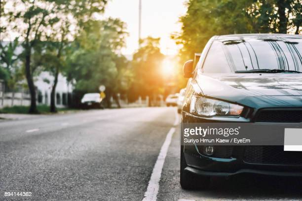 close-up of car on road against sky - motor vehicle stock photos and pictures