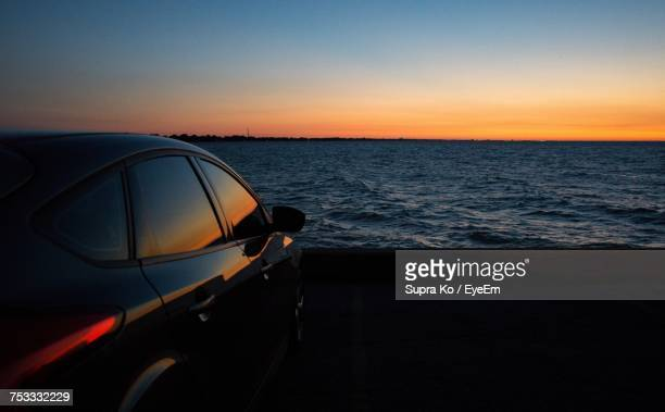 Close-Up Of Car On Sea Against Clear Sky During Sunset