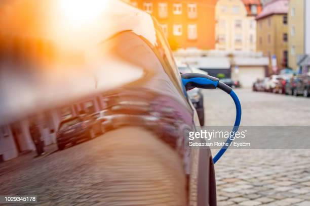 close-up of car refueling on city street - parkplatz stock-fotos und bilder