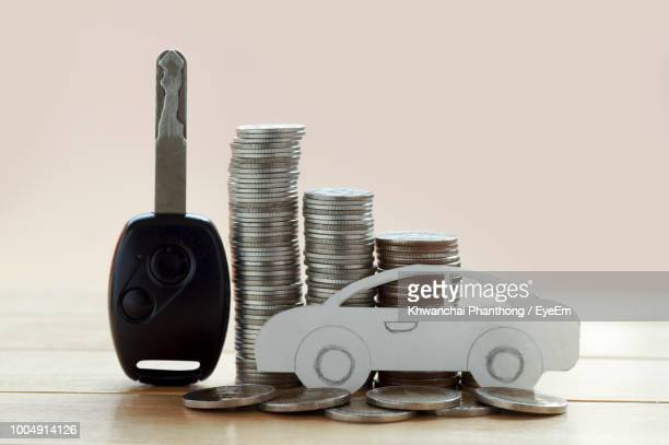 close-up of car shaped paper by coins and key on table - large group of objects stock pictures, royalty-free photos & images