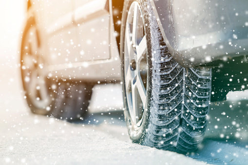 Close-up of car wheels rubber tires in deep winter snow. Transportation and safety concept. 1169524439