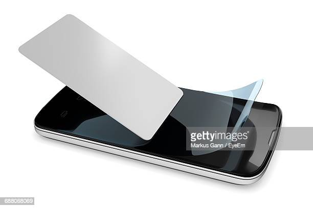 Close-Up Of Card On Mobile Phone With Screen Protector Against White Background