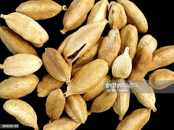 close-up of cardamoms against black background - cardamom stock photos and pictures