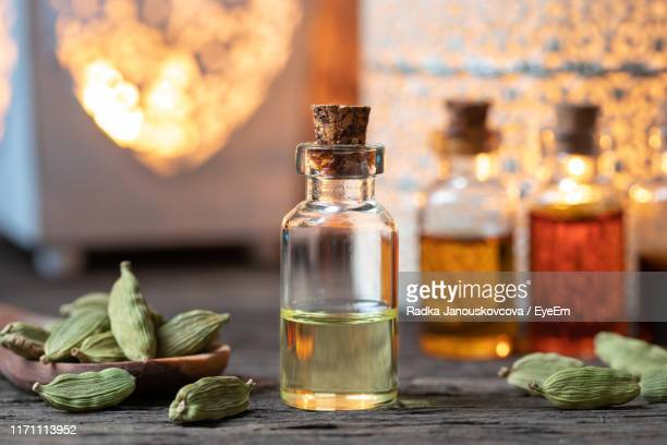 close-up of cardamoms and essential oil on table - aromatherapy stock pictures, royalty-free photos & images