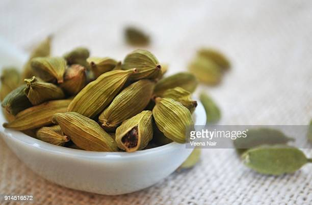 close-up of cardamom/spice in a ceramic spoon - cardamom stock photos and pictures