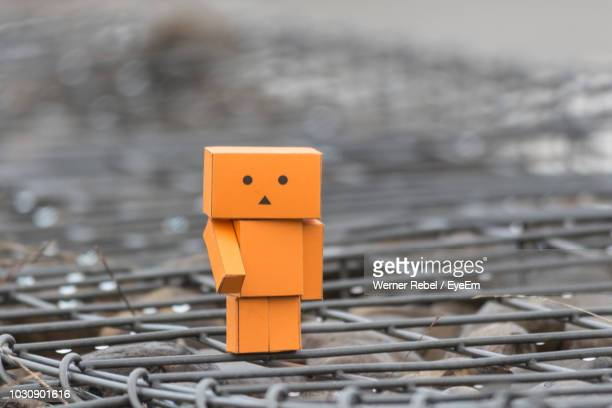 close-up of cardboard toy on metal grate - metal grate ストックフォトと画像
