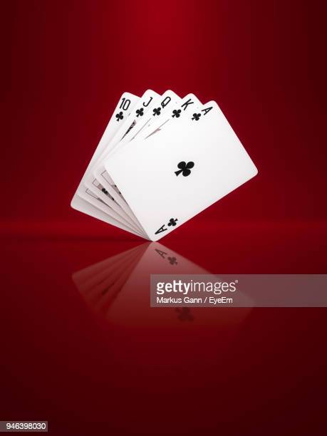 close-up of cards against red background - playing cards stock photos and pictures