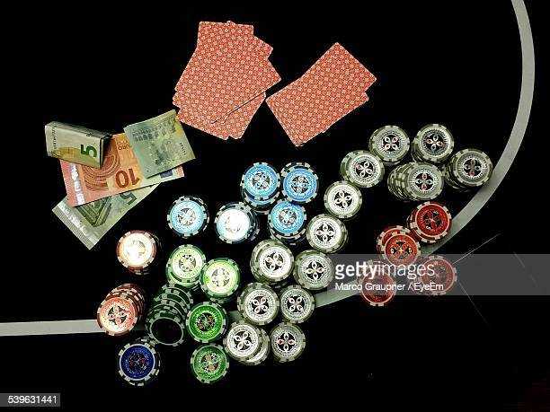 Close-Up Of Cards With Gambling Chips And Currency On Poker Table