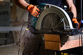 Close-up of carpenter using electric circular saw to cut wood planks